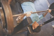 Adam Palmer, a mountain athlete, lifts weights on the bench press during a strength training workout. — Stock Photo