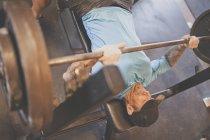Adam Palmer, ein Berg-Athlet, hebt Gewichte beim Bankdrücken während ein Krafttraining training — Stockfoto