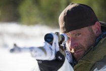 A hunter  takes aim with his rifel, covered in white camouflage tape. — Stock Photo