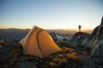 Silhouette di un escursionista su promontorio di roccia mentre il campeggio sulla cima del picco di sassifraga, Pemberton, Canada. — Foto stock