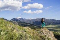 Femme debout sur le rocher et de la recherche sur le paysage de montagnes Montana. — Photo de stock