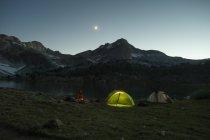 Man sitting near camping in Lakes Basin, California — Stock Photo