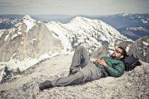 Un excursionista toma una siesta, con su mochila como almohada a la cima del pico de aguja. - foto de stock