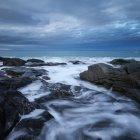 Olas rompen contra la costa rocosa en Skagsanden beach, Flakstad, Flakstady, Islas Lofoten, Noruega - foto de stock
