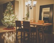 Christmas tree and served table at dining room in residential house — Stock Photo