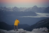 A photographer captures the blue hour from a rocky mountain ridge in Pinecone Burke Provincial Park, British Columbia, Canada. — Stock Photo