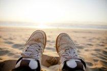 Closeup Beine in Schuhen auf Sand des Strandes — Stockfoto