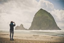 A young woman uses her smartphone to take a picture of Haystack Rock on a cloudy day while visiting Cannon Beach, Oregon. — Stock Photo