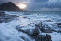 Vagues viennent s'écraser sur la côte rocheuse au cours de la tempête hivernale, îles Lofoten, Norvège — Photo de stock