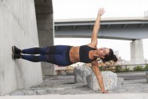 Fit Woman Doing Seite Brett gegen die Wand — Stockfoto
