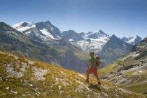 Randonneur à pied vers le haut sur la colline avec les montagnes en arrière-plan — Photo de stock