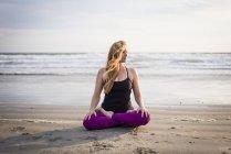 Mujer sentada en la playa haciendo Yoga en Rhode Island en día de viento - foto de stock