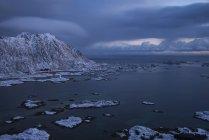 Steinstind montaña pico risies sobre la aldea de Steine en invierno, Vestvgy, Islas Lofoten, Noruega - foto de stock