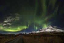 Aurora Boreal sobre el campo y la montaña en Islandia - foto de stock