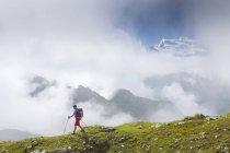 Чоловічий мандрівного на трав'янистих гірської гряди, з хмари навколо Grand поєднувати з гр — стокове фото