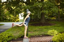 Female Runner Doing Warm Up In Lawn — Stock Photo