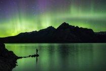Силует людини, що стоїть на озеро і Північне сяйво над озером Minnewanka, Banff, Альберта, Канада — стокове фото