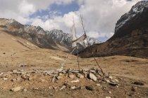 Velhas bandeiras de oração no vento da paisagem rochosa — Fotografia de Stock