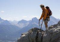 Mountaineer throws rope, mountain range — Stock Photo