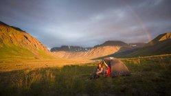 Une femme est assis près de sa tente comme un arc-en-ciel Arcs au-dessus de Camp dans le Parc National de Lake Clark — Photo de stock
