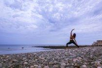 Красивая молодая женщина в обратном воин, делают йоги на закате — стоковое фото