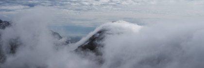 Низкие облака скрывают гор и фьордов с вершины пика горы Volandstind, Flakstady, Лофотенских островах, Норвегия — стоковое фото
