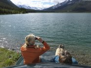 Пара сидить на капот вантажівки і використовує Бінос через озеро — стокове фото