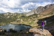 A woman standing on a rocking outcrop and over looks Cecret Lake while hiking down from rock climbing on a summer evening. — Stock Photo