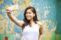 Junge Frau macht Selfie mit ihrem Smartphone — Stockfoto