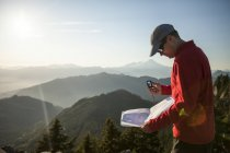 A man uses a compass and paper map to navigate while hiking in the North Cascade Mountain Range. — Stock Photo