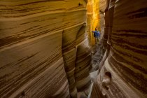 Une femme de randonnée à travers Zebra Slot Canyon près de l'orifice dans l'Utah Rock Road, Monument National de Grand Staircase-Escalante, Escalante — Photo de stock