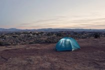 Tent glows at twilight deep in the Canyonlands National Park backcountry — Stock Photo