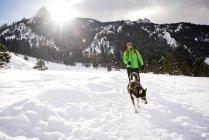 Парень и его собака на солнечный зимний день ходьбы через парк Чаутоква в Боулдер, Колорадо — стоковое фото