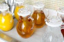 Gläser mit Fruchtsaft füllen verstauen auf einer Küchenarbeitsplatte — Stockfoto