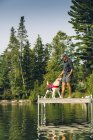 Man with dog on edge of dock on Caspian Lake — Stock Photo
