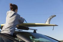 Woman taking surf board off car roof — Stock Photo