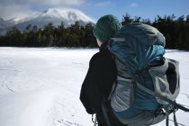 A young Woman pauses while snowshoeing through Baxter State park to take in a windswept view of Mount Katahdin. — Stock Photo