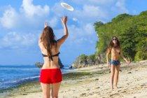 Ragazze giocare a frisbee e avendo divertimento alla spiaggia. — Foto stock