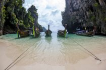 Six wooden long tail boats anchored to a small sandy beach on a island in Krabi, Thailand — Stock Photo