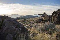 Людина піднімає його рушниці полювання на кеклика. — стокове фото