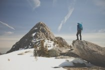 Photograph of hiker looking at view of Needle Peak in winter, British Columbia, Canada — Stock Photo