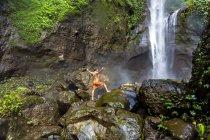 Uomo senza camicia in pantaloncini in piedi sulle rocce vicino alla cascata, Kintamani, Bali, Indonesia — Foto stock