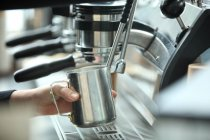 Cropped shot of coffee maker holding silver cup while making coffee — Stock Photo