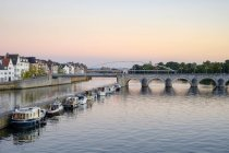 Photograph of Meuse River with bridge, boats and buildings on bank, Maastricht, Limburg, Netherlands — Stock Photo