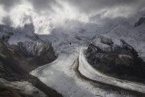 Чорно-біле фото alpine птах, летить відкриті крила вище льодовик зі світла, що проходить через хмари — стокове фото