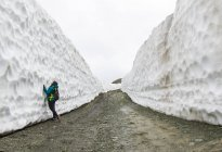 A woman stares up at a wall of snow on Whistler Blackcomb, on a gloomy spring day, were the road has been cleared for the spring. Snow walls over 20 feet tall line both sides of the road. — Stock Photo