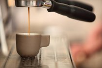 Side view of coffee pouring into espresso cup from coffee machine — Stock Photo