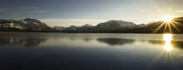 Sunrise over mountains and lake in winter — Stock Photo
