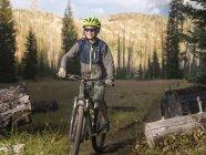 Jeune garçon conduisant le vélo de montagne sur le sentier dans la forêt — Photo de stock