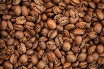 Vue de dessus des grains de café torréfiés comme toile de fond — Photo de stock